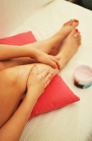 image of hands applying lotion to legs