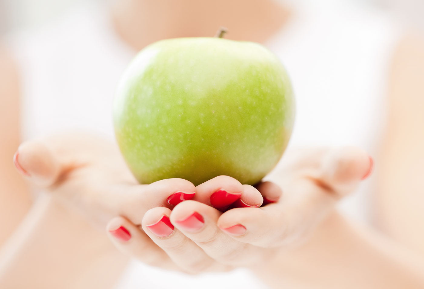 image of woman holding green apple
