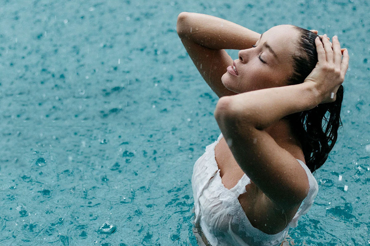 image of clothed woman in a pool of water pulling wet hair back