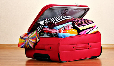 over stuffed suitcase, packing essentials tips and tricks to packing for a festival