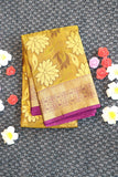 Mustard green silk saree with floral motifs and purple colour border and pallu