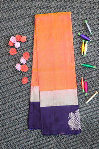 Peachish orange colour soft silk saree with blue colour border and silver zari buttas in border