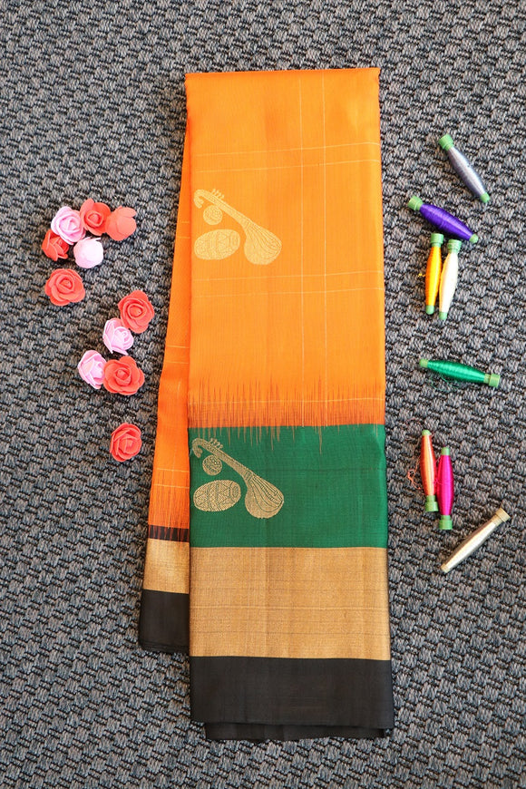 Reddish orange soft silk saree with traditional musical instruments motifs with contrast blouse and border