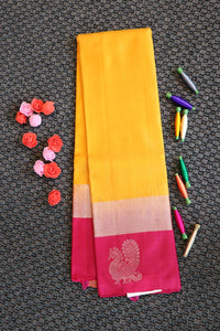 Yellow colour pure soft silk saree with pink colour border and blouse with silver zari motifs on border