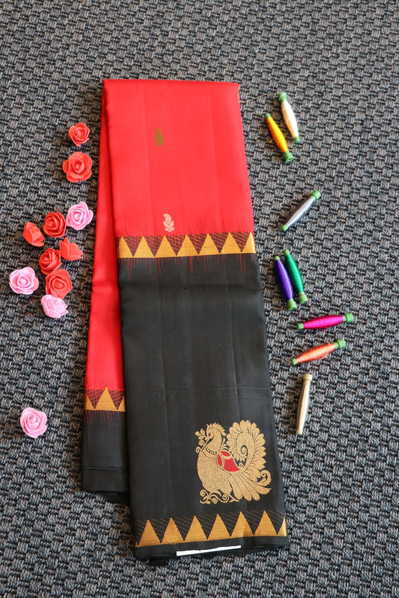 Red colour pure soft silk saree with big black border with gold and silver zari peacock motifs