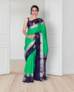 Olive green soft silk saree with silver zari peacock design on blue colour border and pallu