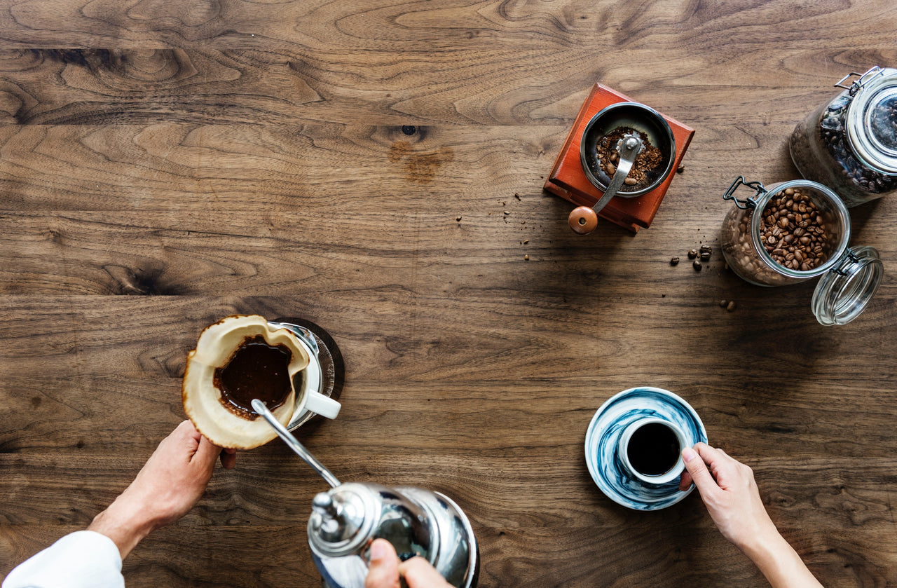 overhead view of coffee and coffee making implements on wooden table