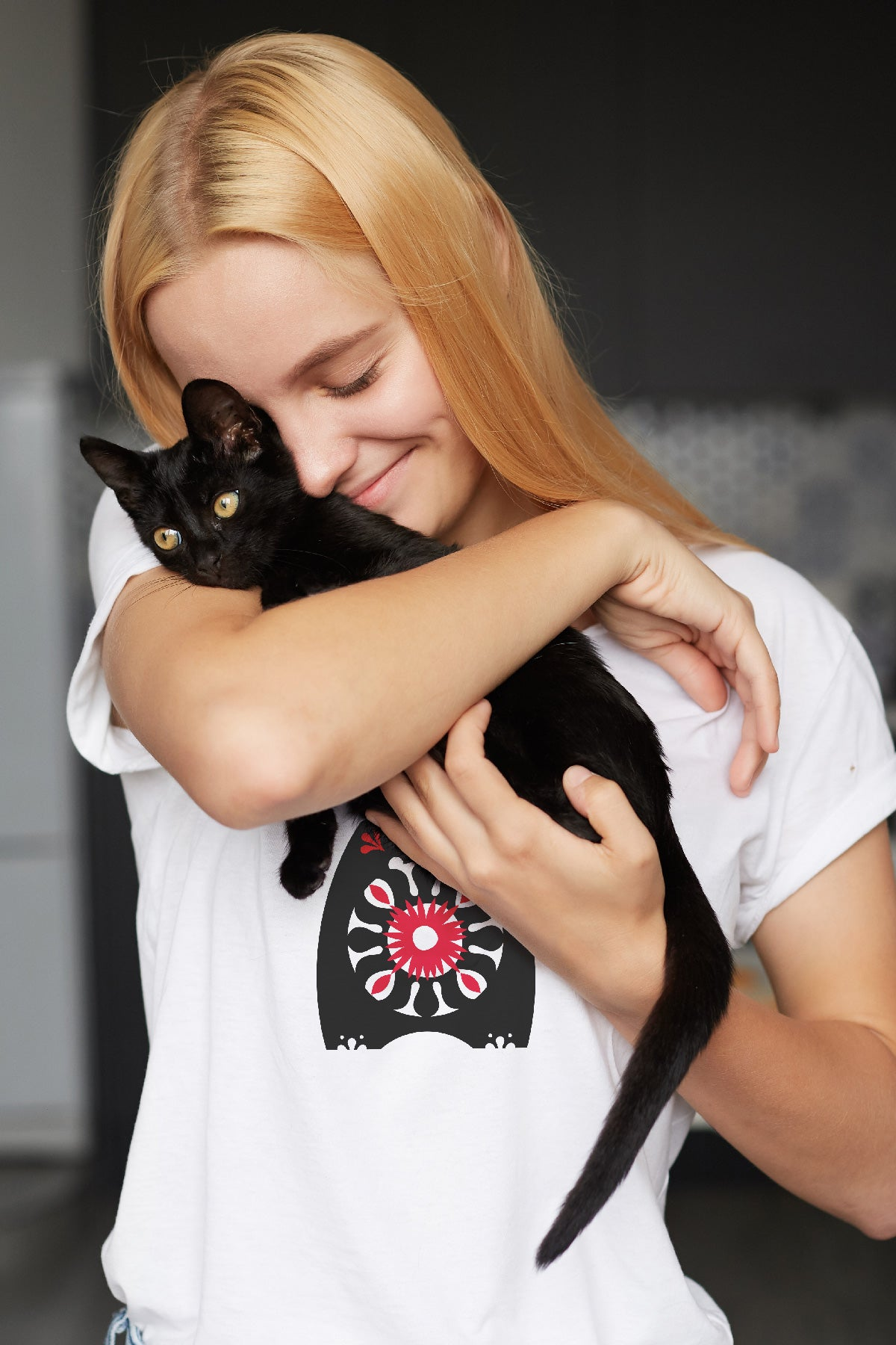 Woman wearing Behemoth t-shirt and holding a black kitten.