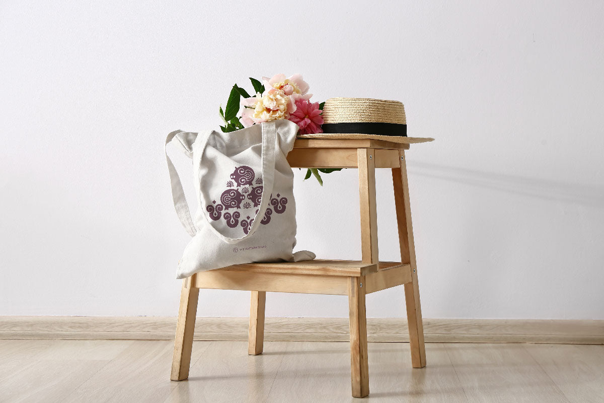 Circe tote bag on a chair with summer flowers and a straw hat.