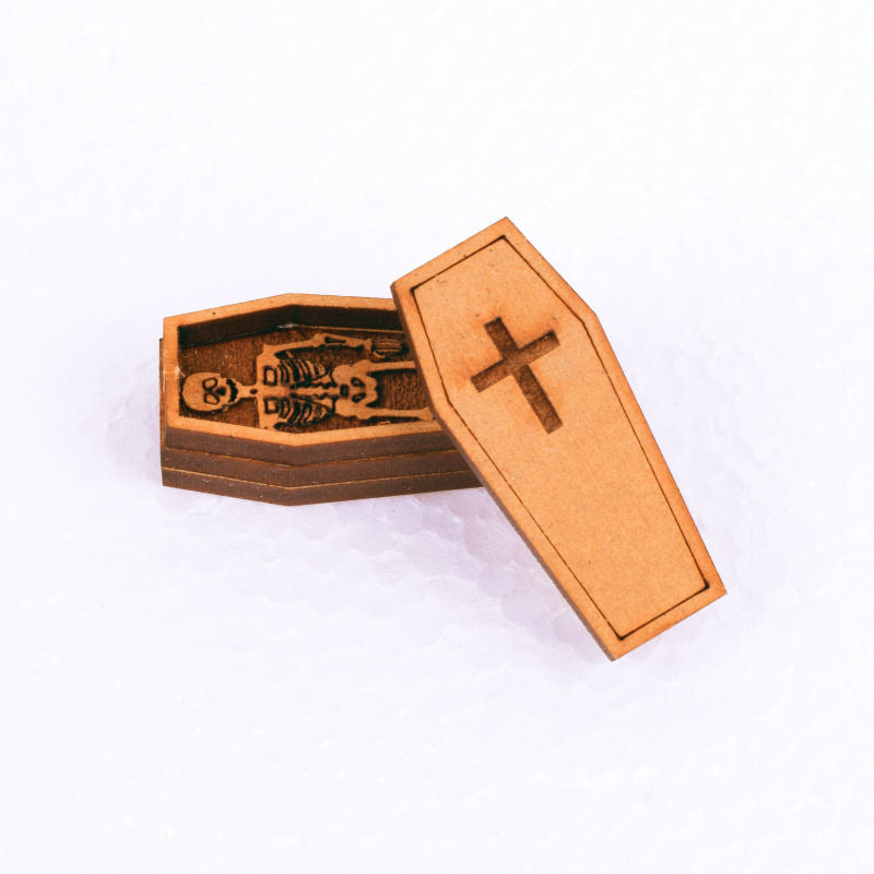 miniature coffin with cross on lid and skeleton inside