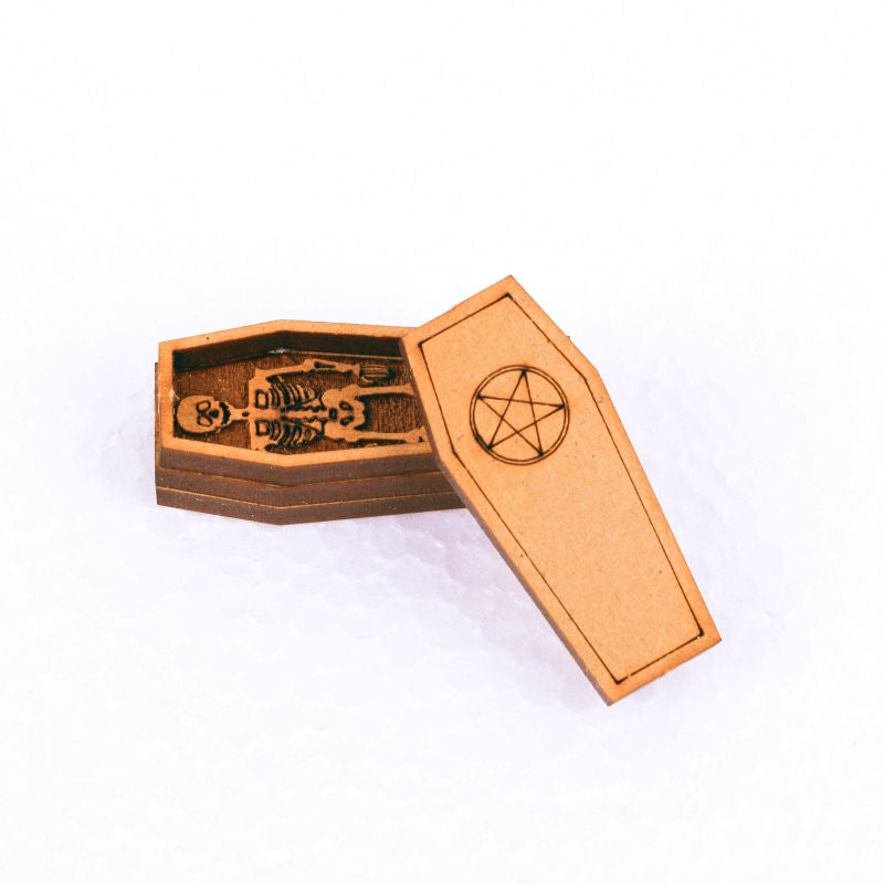 miniature coffin with pentagram on lid and skeleton inside