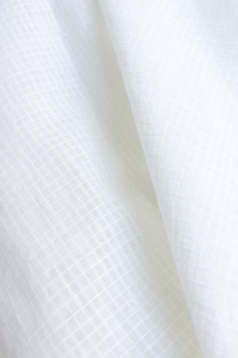 Taylor Tall close up of cream fabric for drop shoulder button up top for tall women.