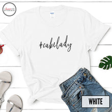 Load image into Gallery viewer, #cakelady white tshirt on wood background