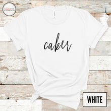 Load image into Gallery viewer, white caker tshirt mockup on light wood background