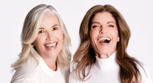 Two Women Laugh About Menopause Taboos, Both Women Look Very Happy, they wear white clothe. Woman at the left has gray long hair and woman at the right has long way brown hair. Both women are over 40 years old.
