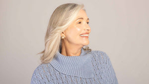 A woman over 50 feels great about her hair which is dry no more. She is wearing a purple knit sweater and has blonde medium hair. She smiles and looks to one side while we can see she's wearing beautiful luxurious earrings.