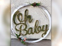 Woodland theme decorate Oh baby cutout sign placed on floor leaning against wall