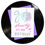 the words go shawty it's your birthday in shiny holographic rainbow foil with pink accents & a shiny disco ball for the o on top of a purple envelope. block printing by Niki Baker with foreignspell from hand-carved stamps & song lyrics.