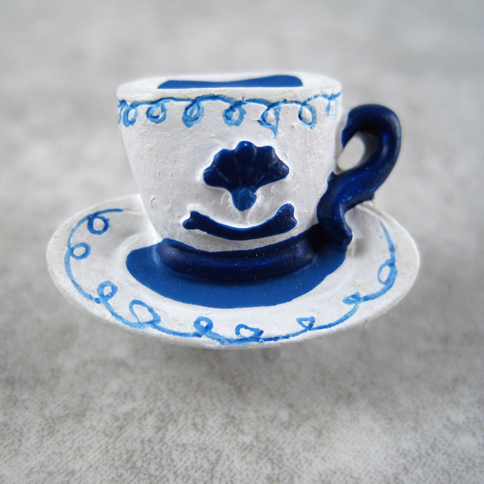 A white cup and saucer button