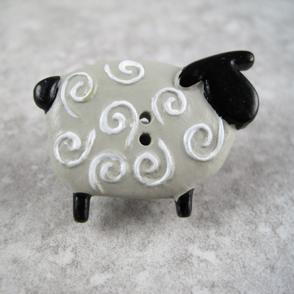 Sheep button with black head and tail.