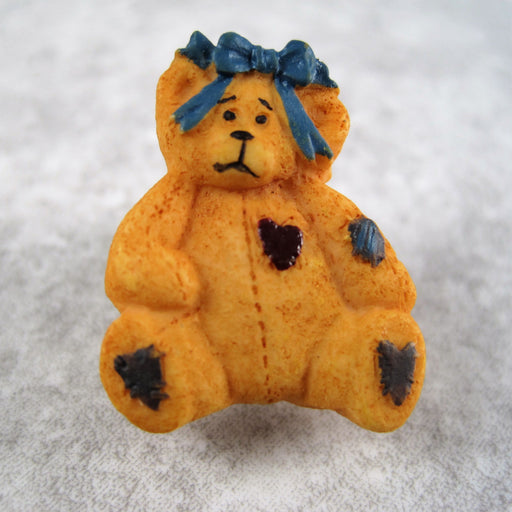 A tan bear with hair bow.