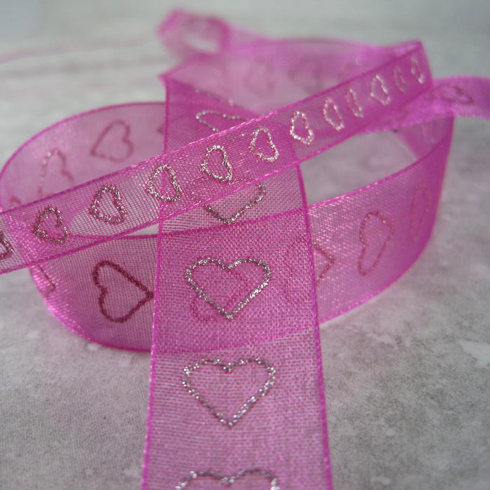 Sheer magenta ribbon, with a sparkly, silver, heart shaped motif