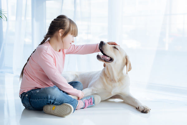 young girl in pink shirt sitting on floor petting her yellow labrador retriever
