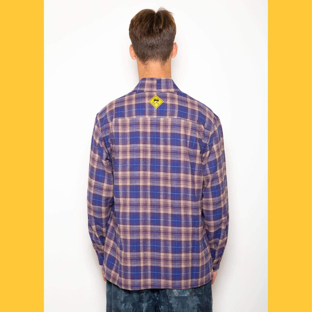 "The Skidz Plaid Flannel Smoking Jacket is a modern take on the classic smoking jacket. It has a draped fit with deep pockets on both sides. It can be worn open or buttoned.   Model is 6' 2"" and wearing a large.  All Skidz garments are produced on a limited run. Each fabric is unique and limited in availability and may not be reproduced again.  -- Baymen Purple plaid  deep side pockets unisex 100% cotton flannel made in the US"
