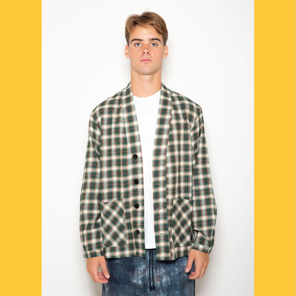 "The Skidz Plaid Flannel Smoking Jacket is a modern take on the classic smoking jacket. It has a draped fit with deep pockets on both sides. It can be worn open or buttoned.   Model is 6' 2"" and wearing a large.  All Skidz garments are produced on a limited run. Each fabric is unique and limited in availability and may not be reproduced again.  -- Hunter Green plaid  deep side pockets unisex 100% cotton flannel made in the US"