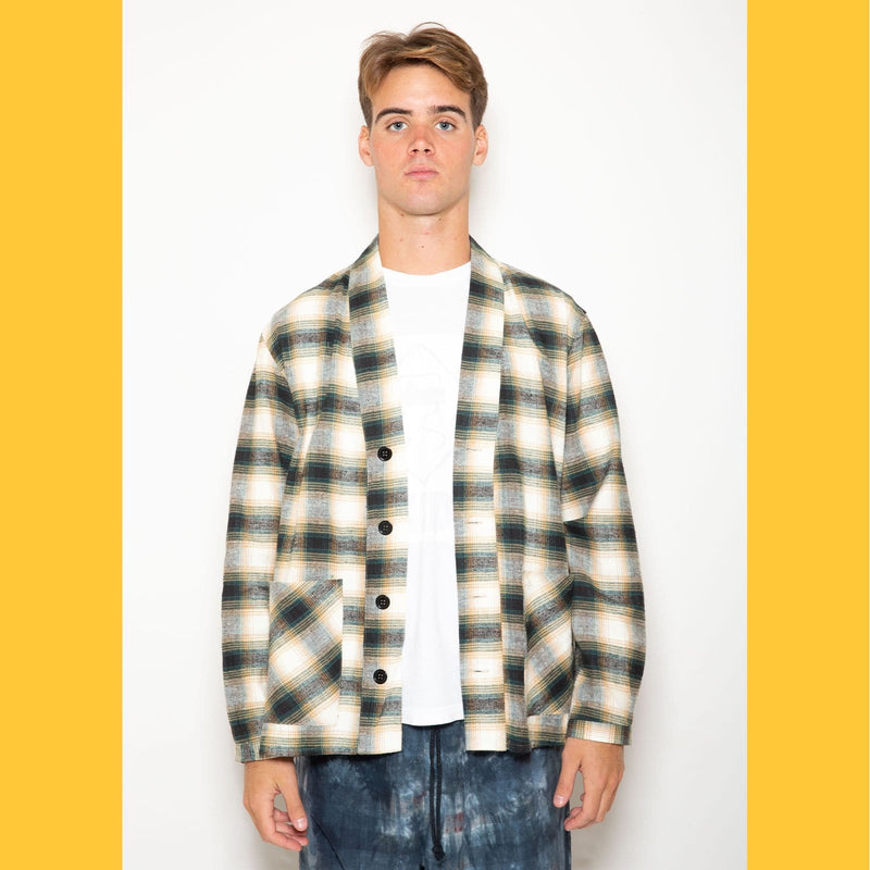"The Skidz Plaid Flannel Smoking Jacket is a modern take on the classic smoking jacket. It has a draped fit with deep pockets on both sides. It can be worn open or buttoned.   Model is 6' 2"" and wearing a large.  All Skidz garments are produced on a limited run. Each fabric is unique and limited in availability and may not be reproduced again.  -- Hunter Ombre plaid  deep side pockets unisex 100% cotton flannel made in the US"