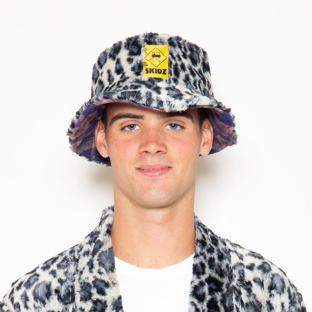 The reversible bucket hat is Baymen Purrple plaid flannel on one side and Snow Leopard faux fur on the other side.  Snow Leopard is a faux fur material that is super soft, comfy, and cozy.   reversible bucket hat faux fur and flannel one size made in the US