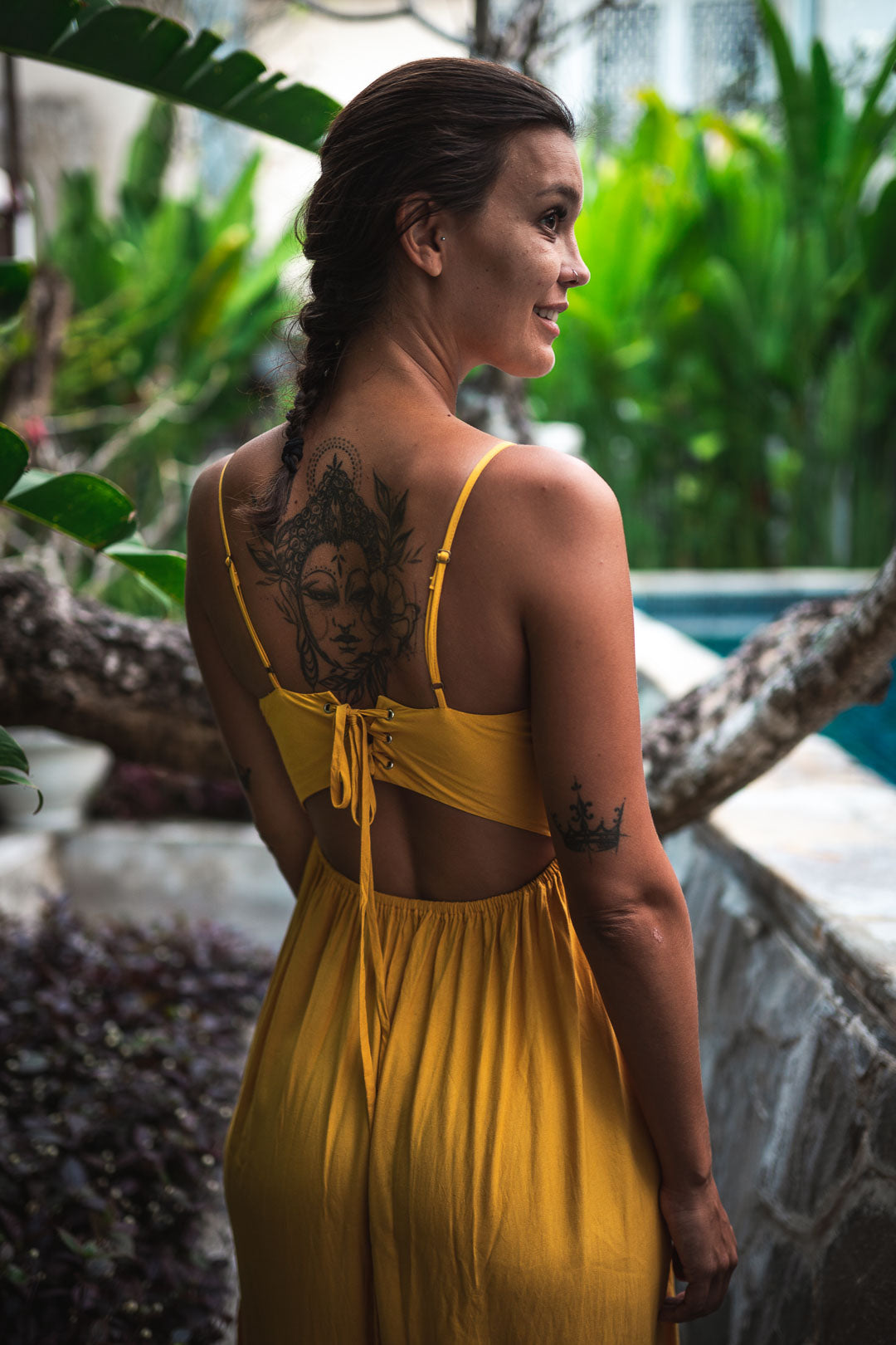 Brunette and tattooed woman in yellow dress near swimming pool