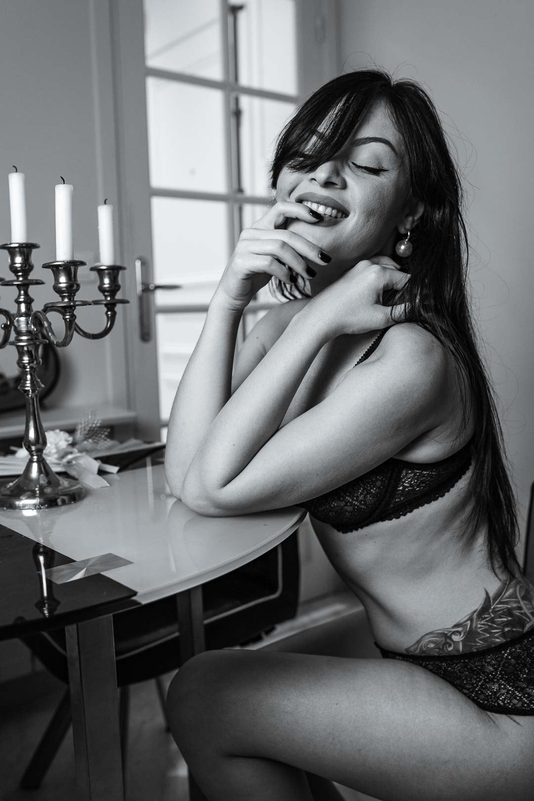 Black and white photograph of a smiling boudoir-style woman