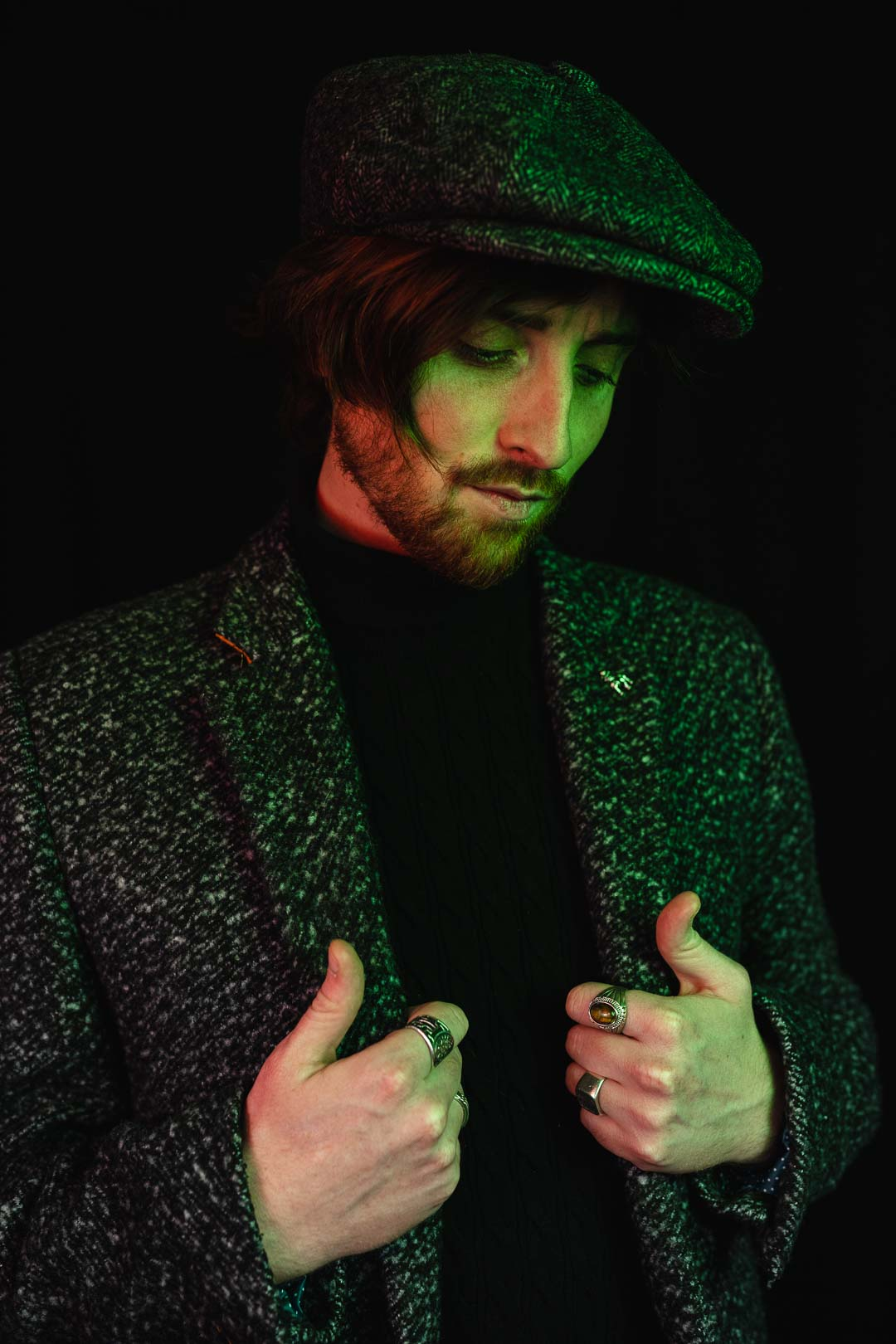 Portrait of a man dressed in a tweed jacket on a black background with green light reflections