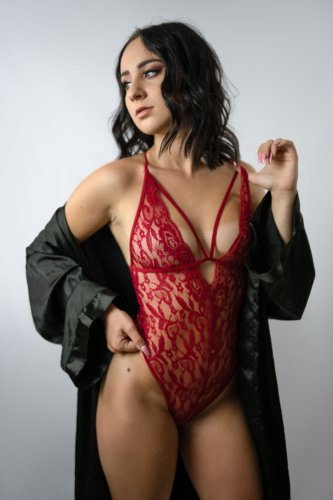 Brunette woman in red lingerie and bathrobe in a photo studio