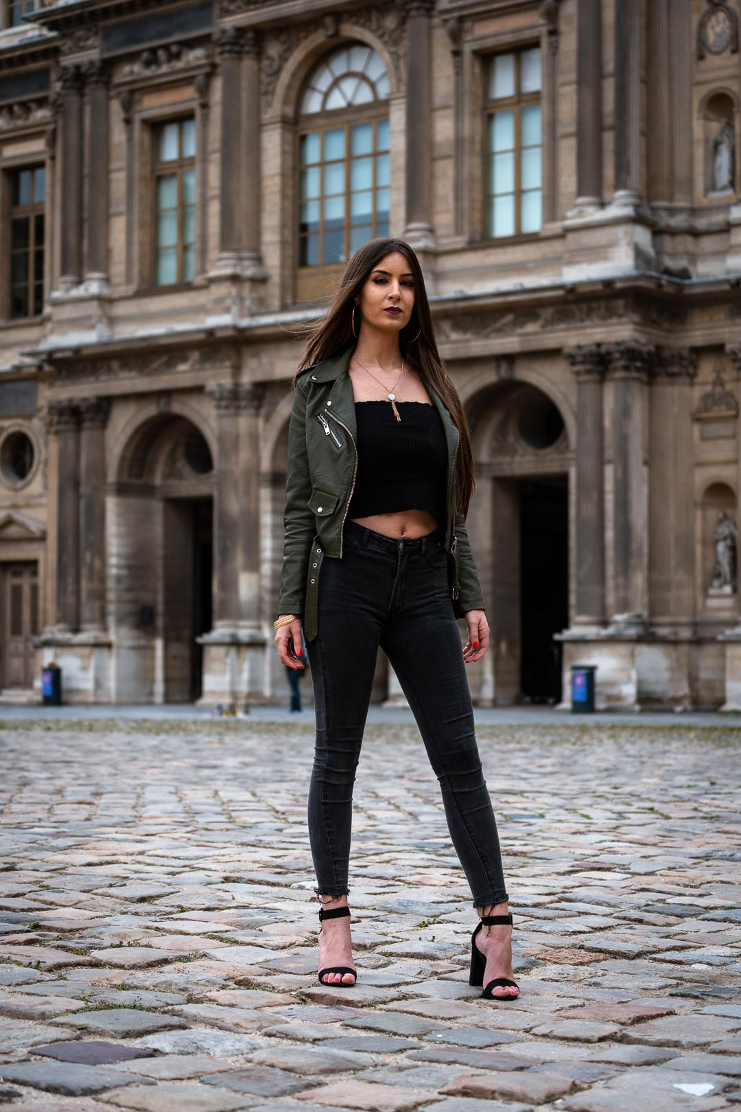 Woman in urban attire standing in front of the Louvre castle