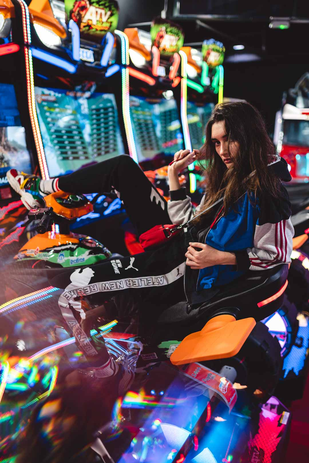 Young woman in jogging sitting on a retro gaming machine in an arcade