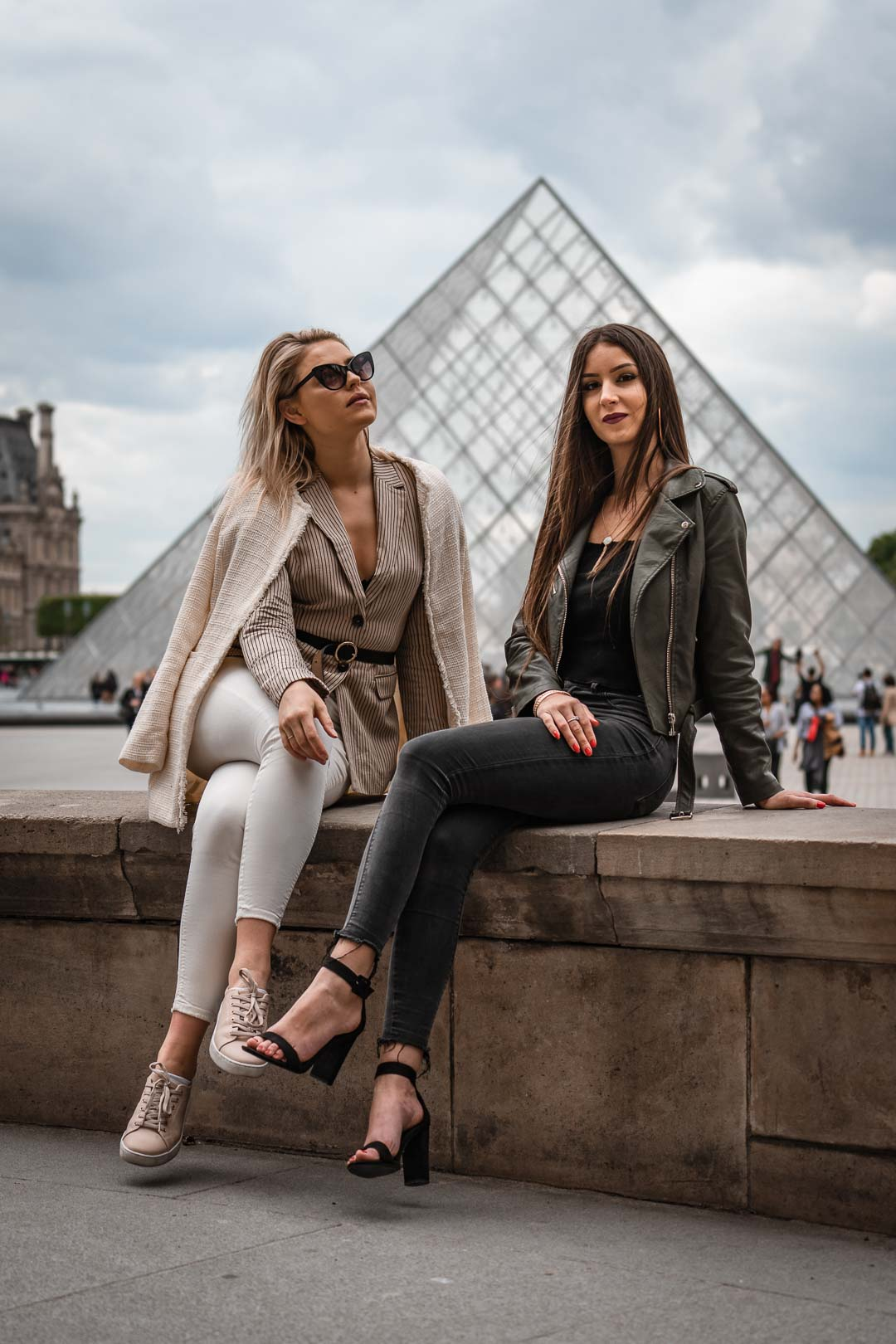 Photograph of two women seated in front of the Louvre pyramid