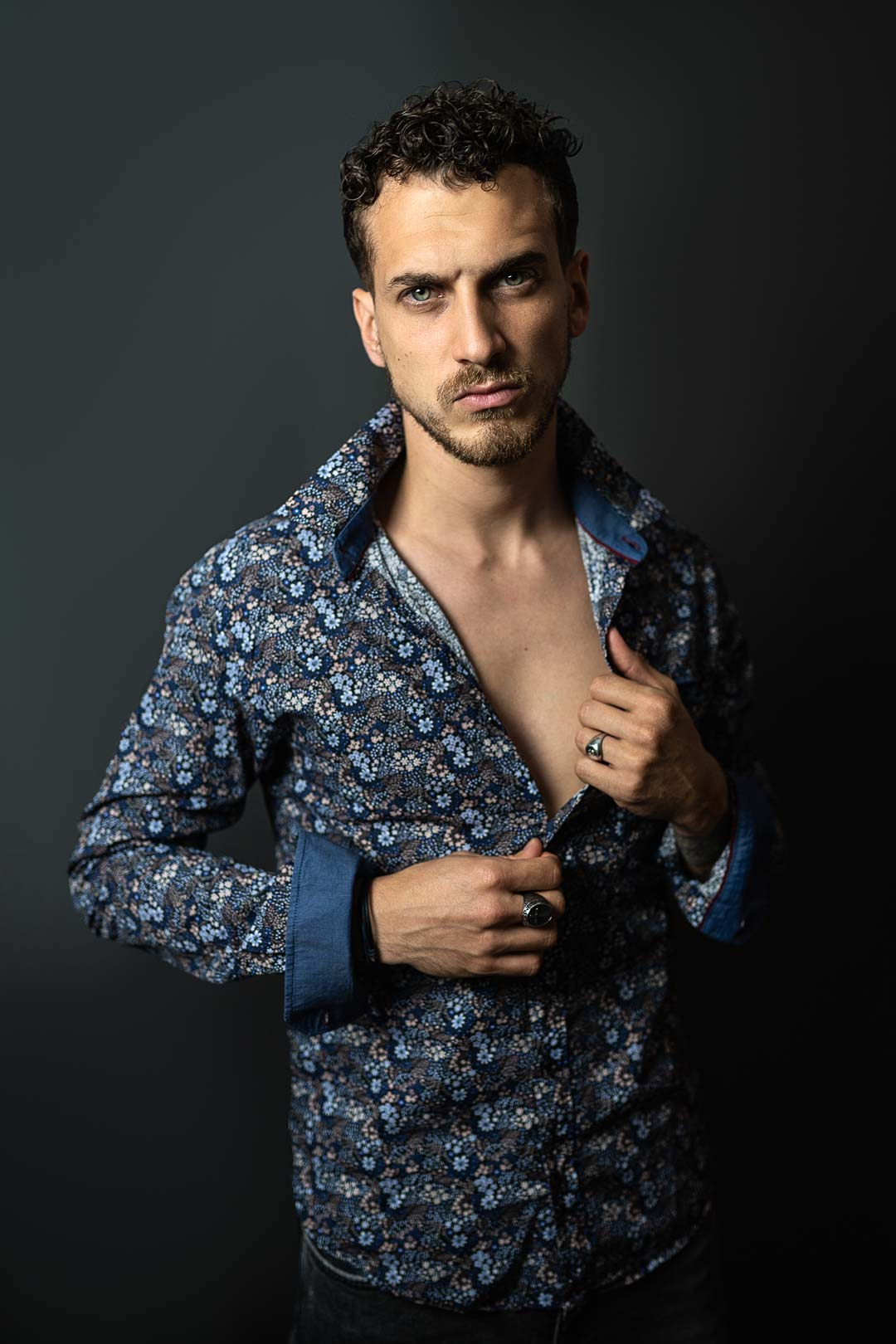 Male model unbuttoning his shirt in a photo studio
