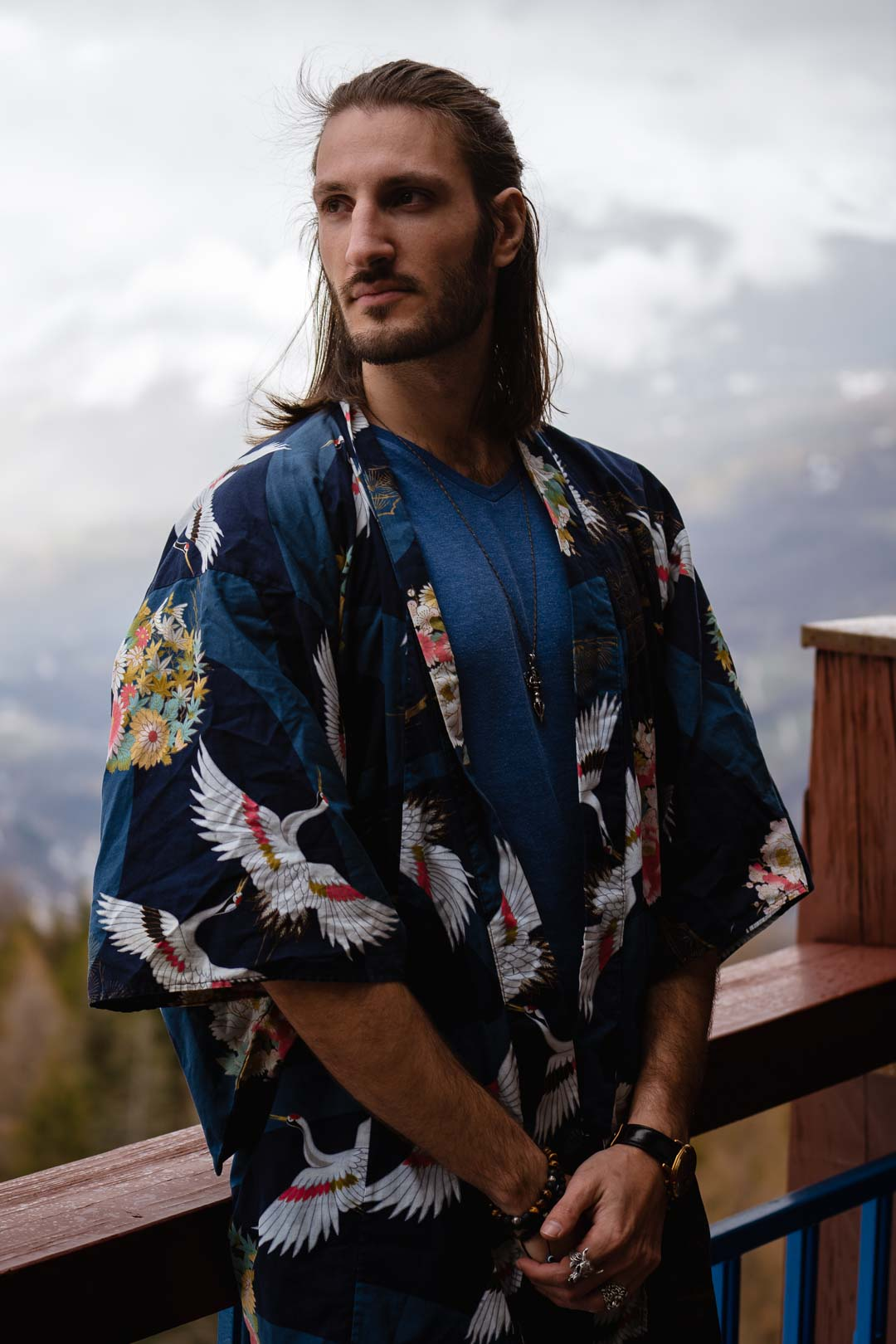 Man with long hair wearing a kimono in front of a snowy landscape