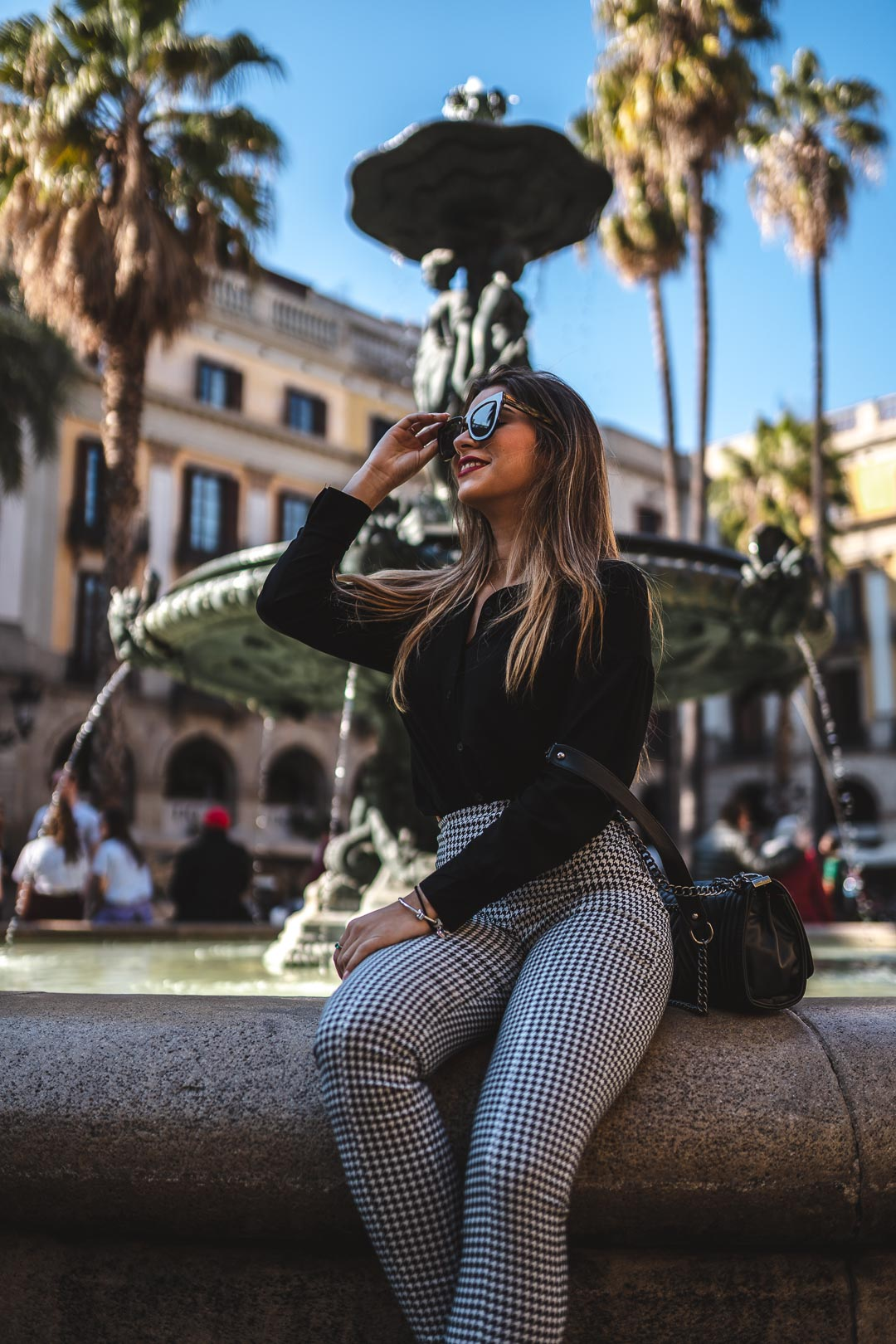 Woman wearing sunglasses sitting on the Plaça Reial fountain in Barcelona