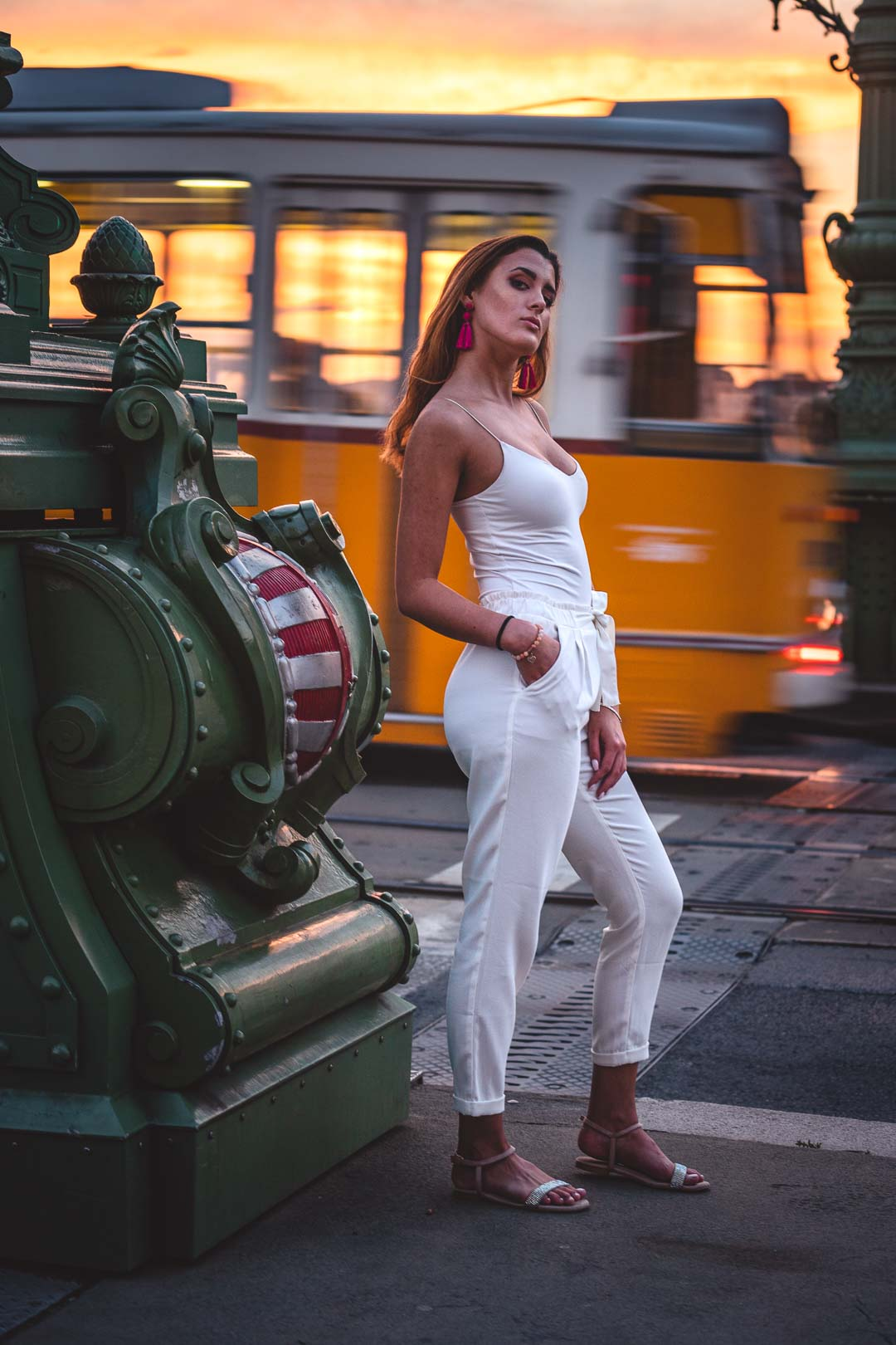 Hungarian woman in white in front of a rolling tram