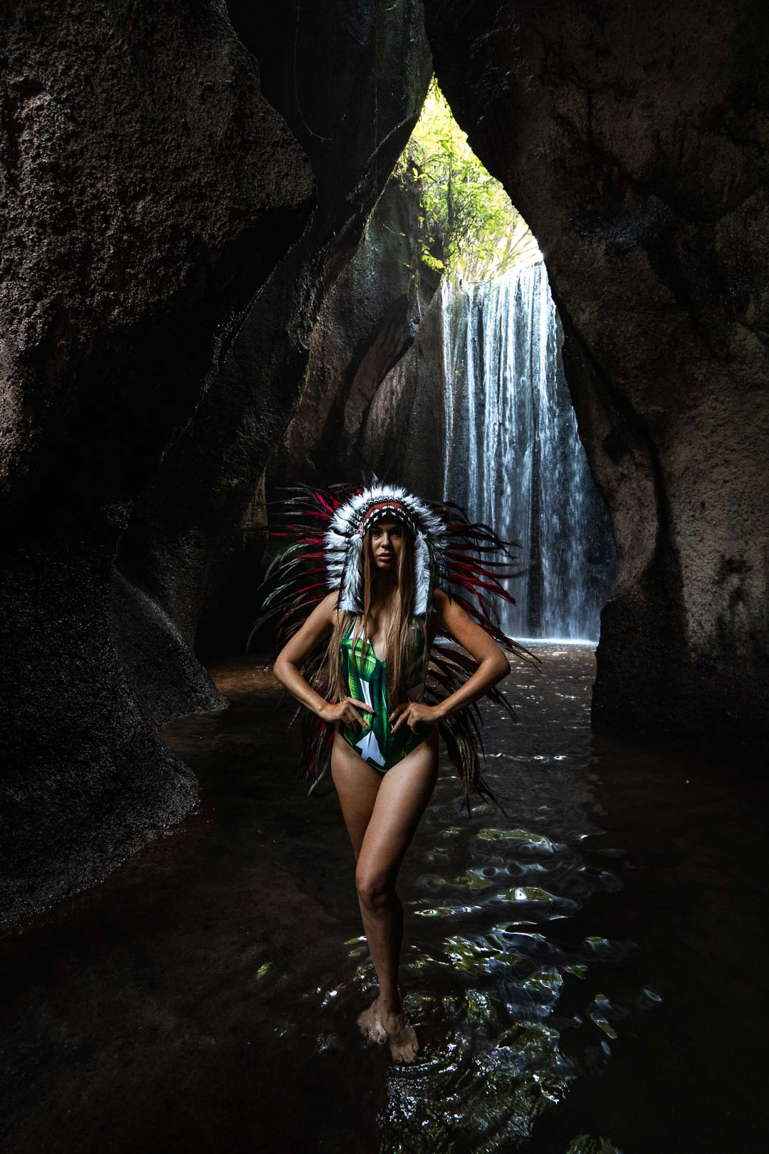 Photograph of a woman with an Indian headdress in a waterfall