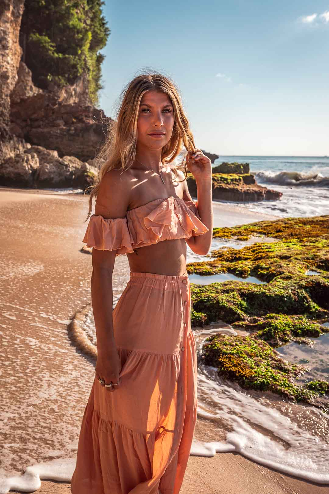 Photograph of a model in a pink dress on the beach