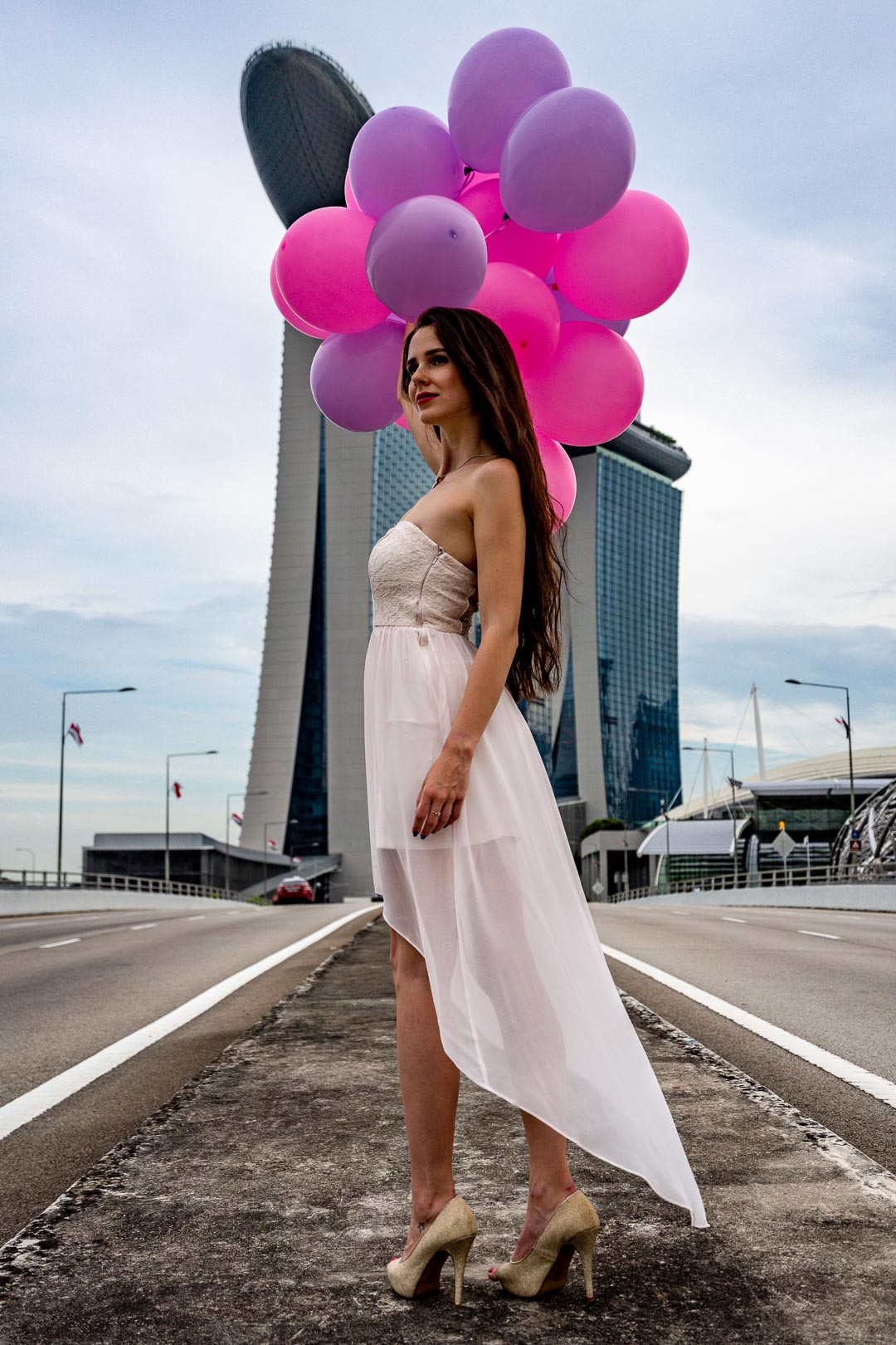 Female model poses with colorful balloons in front of Marina Bay Sands in Singapore