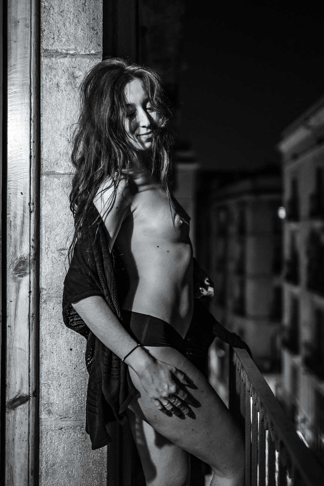 Artistic nude photograph of a woman on a balcony