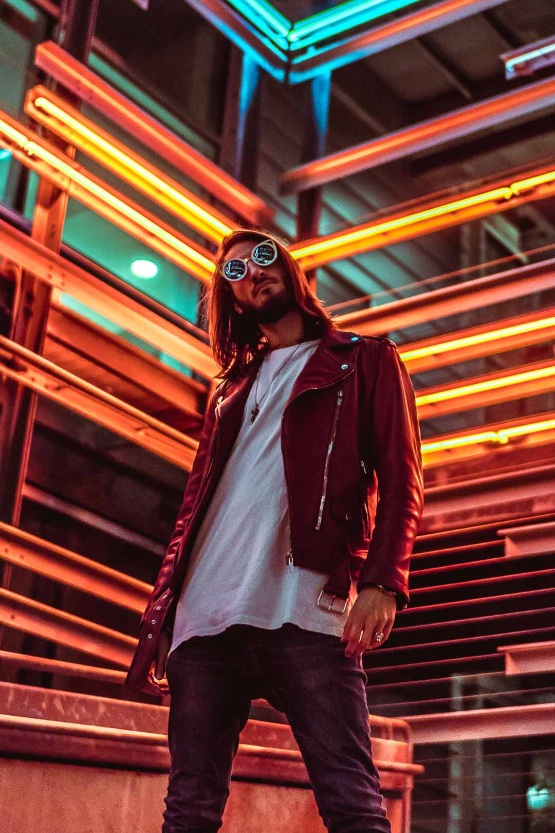 Male model wearing red leather jacket in front of neon lights in Los Angeles