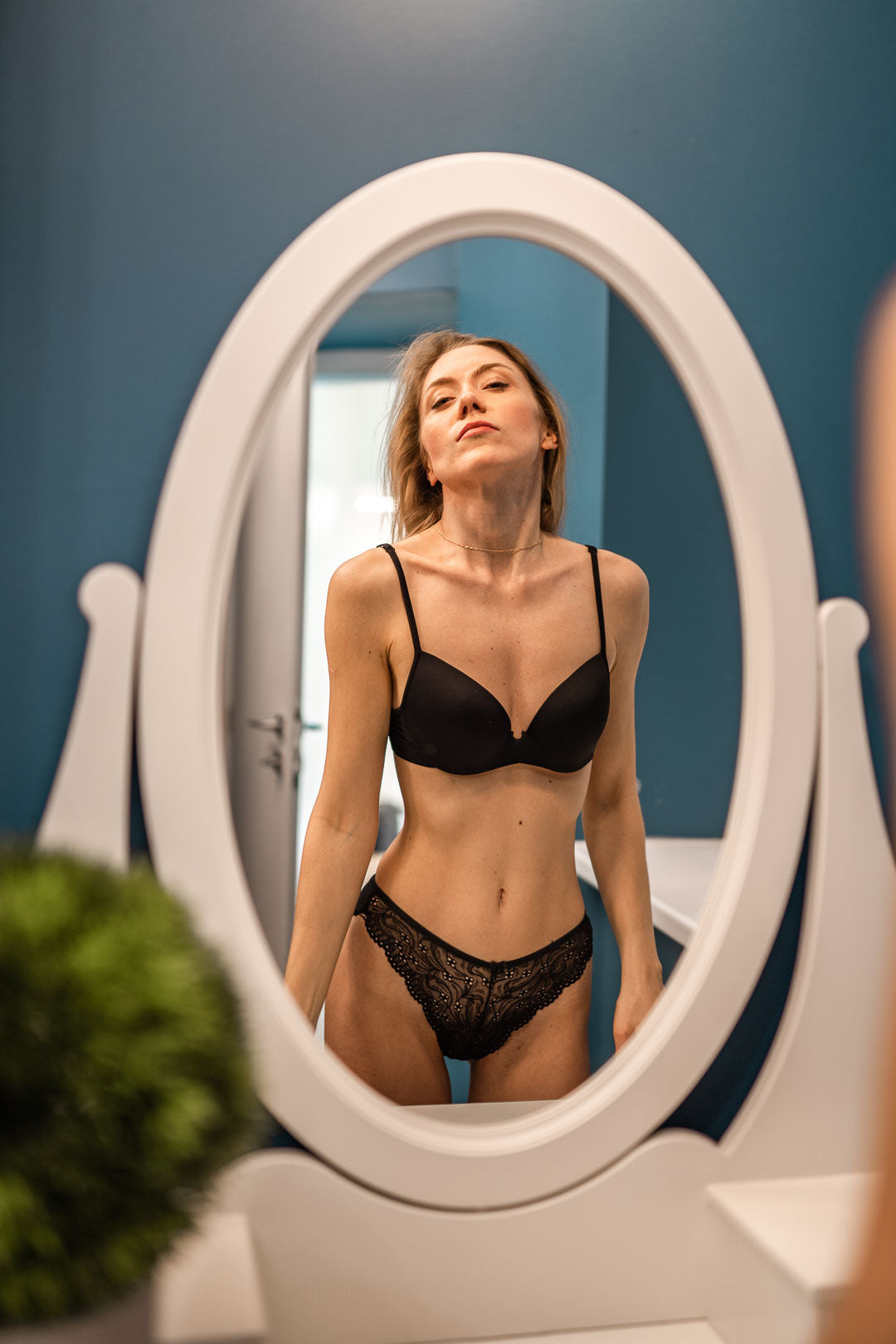Mirror reflection of a woman in black lingerie
