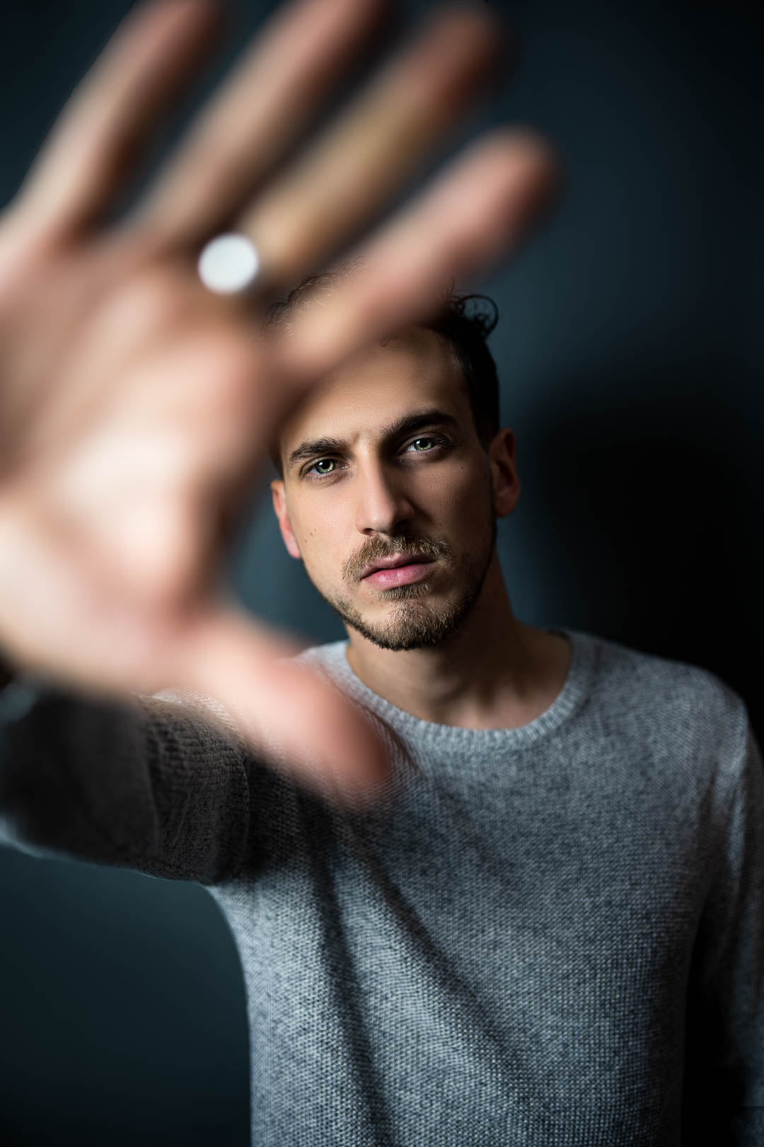 Male model putting his hand in front of the camera lens in a photo studio