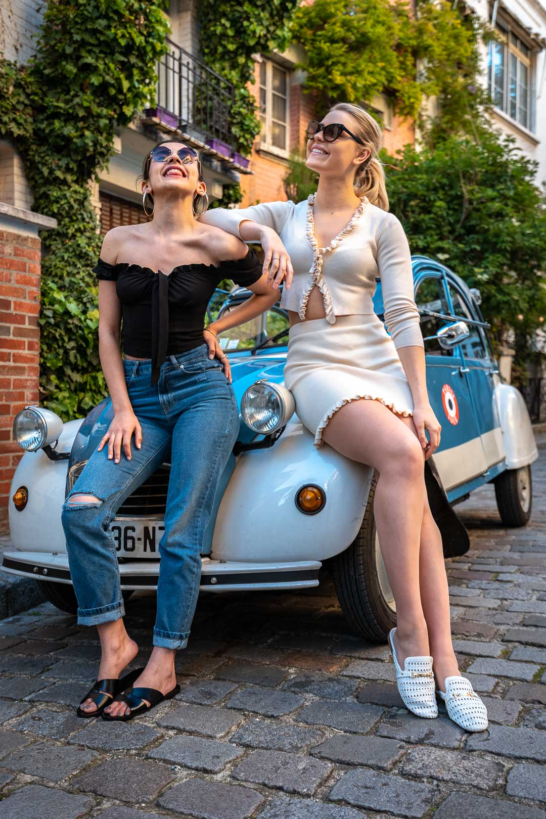 Two friends sitting on the hood of a Citroen 2cv in a cobbled street in Montmartre
